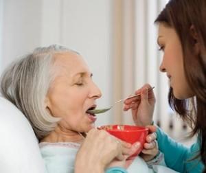 Дочь кормит маму ухаживая при альцгеймере