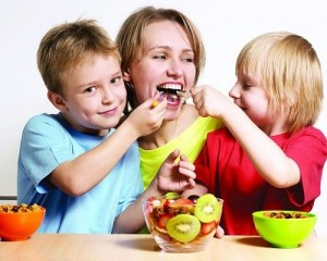 Мама и дети едят фруктовый салат